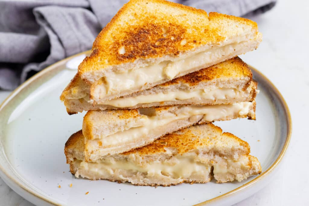 Grilled cheese stacked on a white speckled plate with gray napkin