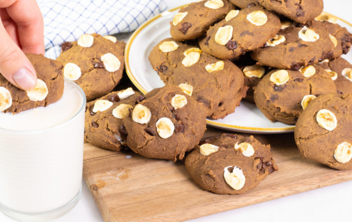Pile of Chocolate Cookies with Marshmallows and Chocolate Chips with one cookie being dipped in almond milk