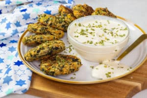 Oil-free Spinach Artichoke Latkes on a plate with vegan sour cream