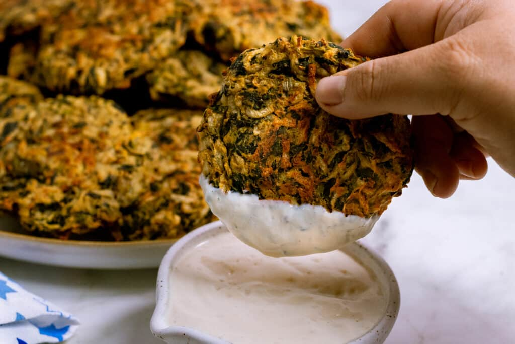 Latkes being dipped in vegan sour cream