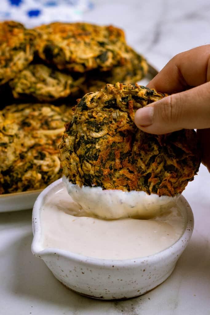 Latkes being dipped in vegan sour cream