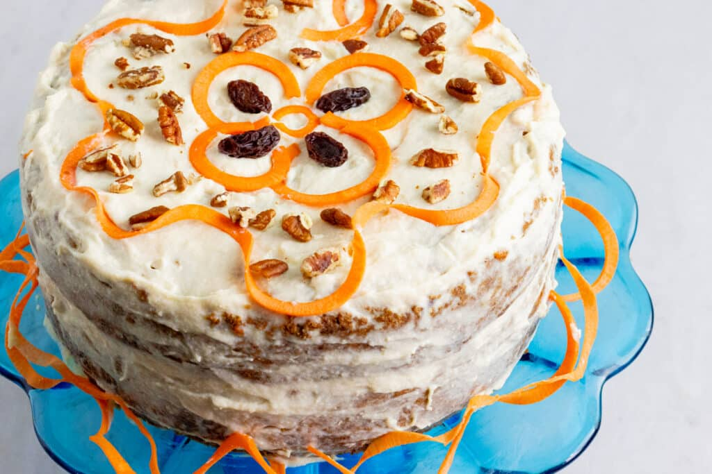 Uncut decorated carrot cake on a blue cake stand