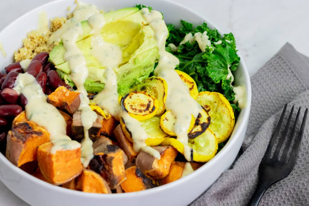 bowl full of sweet potatoes and other veggies with a white dressing