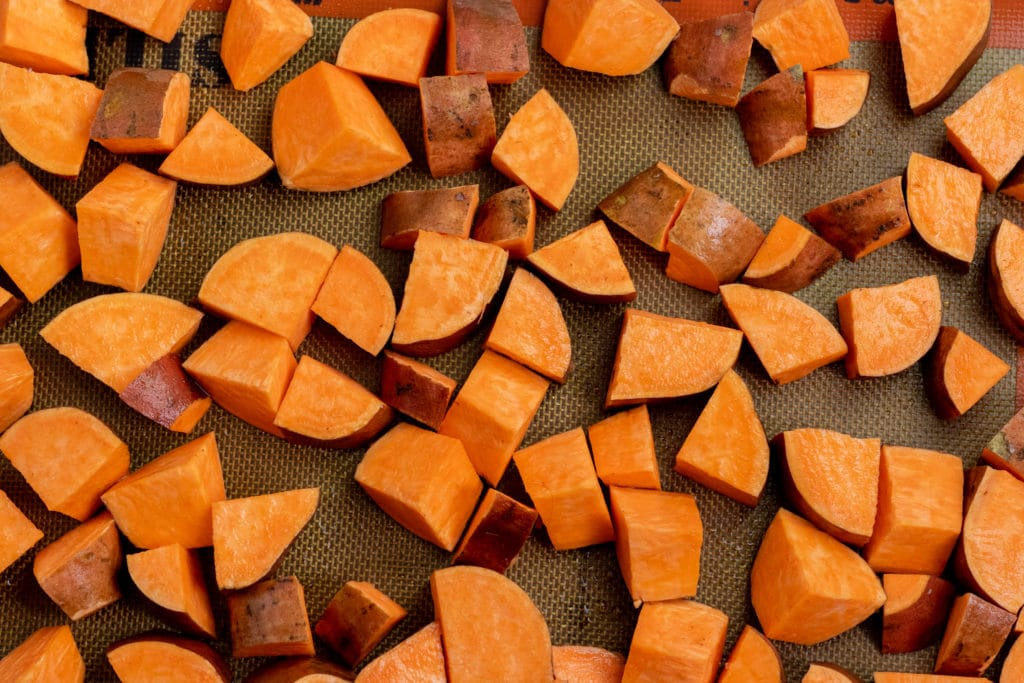 cut sweet potatoes on a baking tray