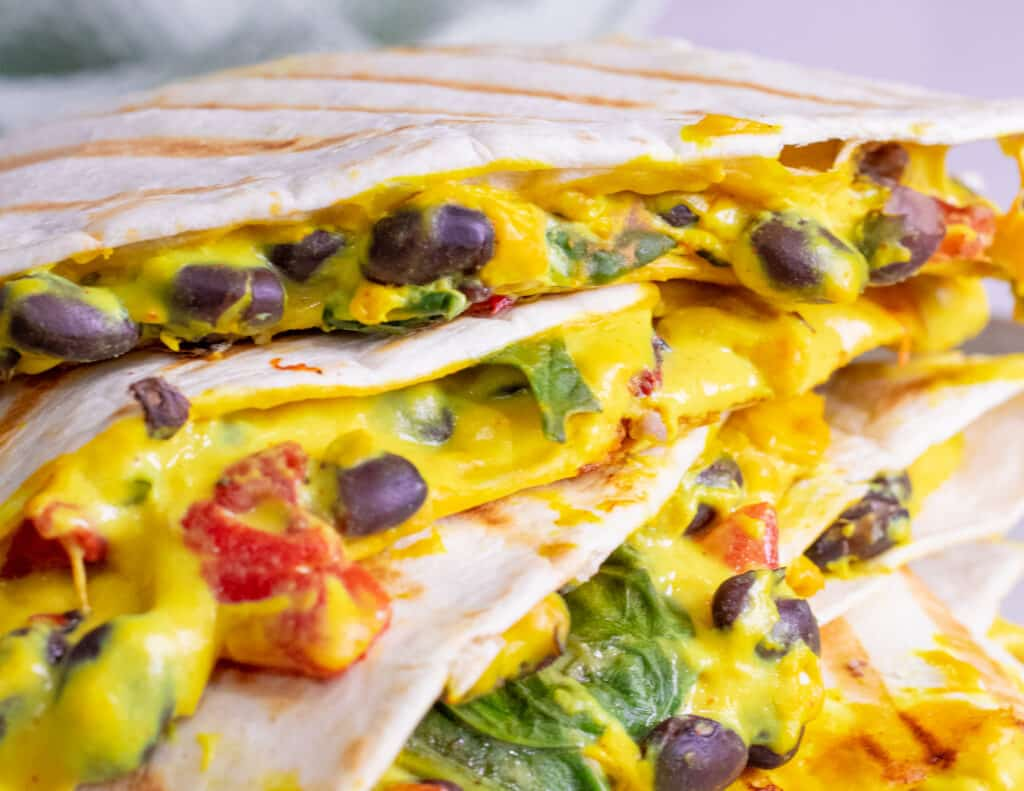 Stacked quesadillas packed with melty cheddar, black beans, tomatoes, and spinach