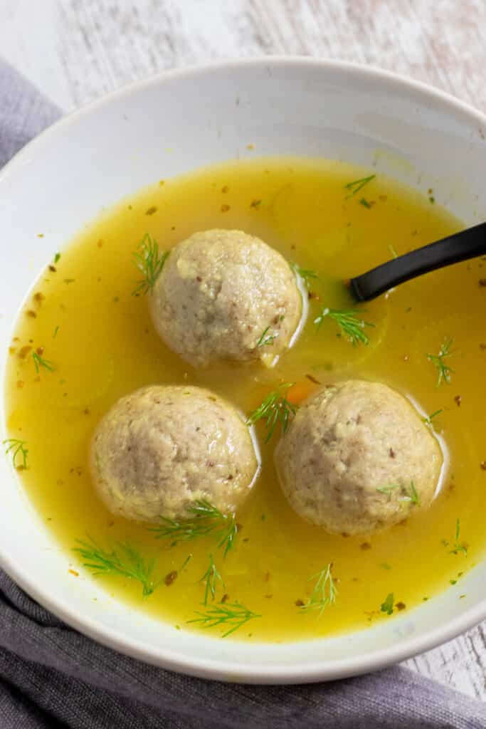 3 matzo balls and broth in a white bowl with a black spoon and a gray napkin