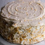 Unsliced coconut cake on a cake stand