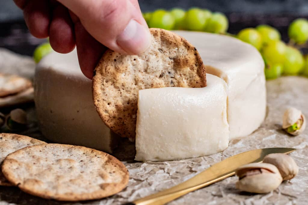 A cracker cutting into soft vegan brie