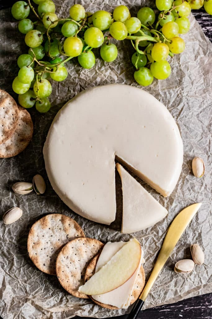 Vegan bree wheel with slice on crackers with apple slivers
