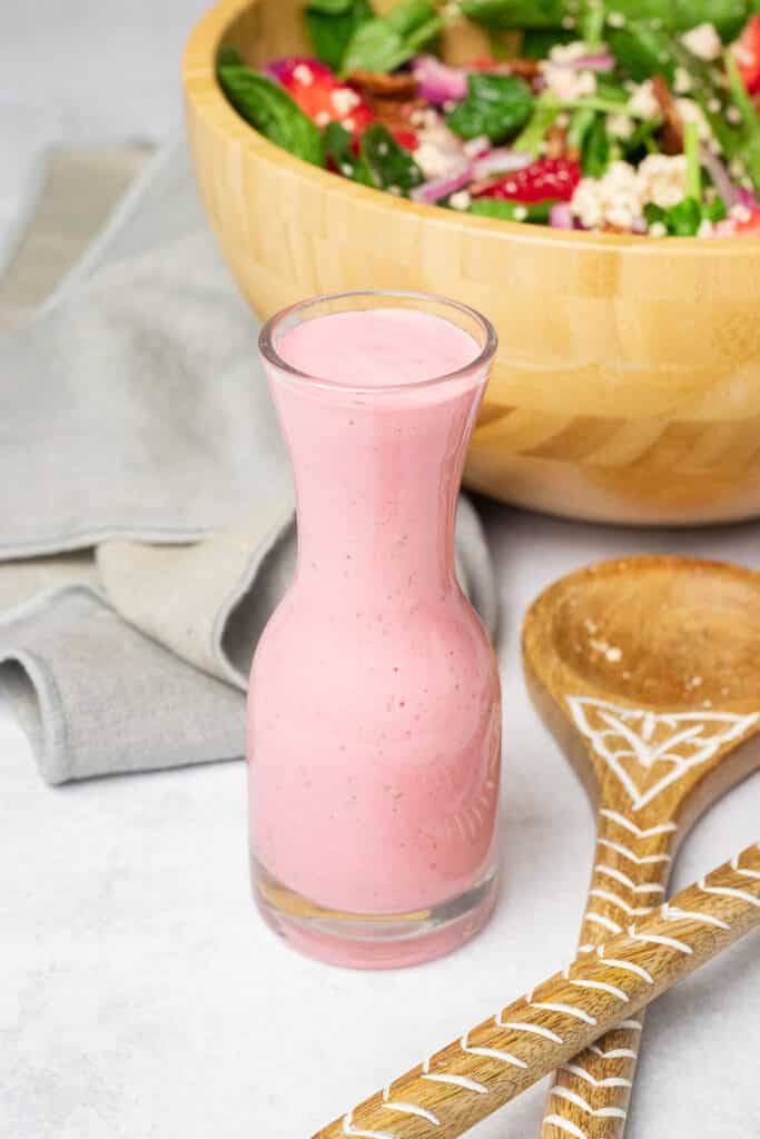 Glass of Strawberry Dressing in front of a salad bowl