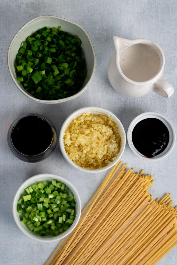 Garlic, green onions, soy sauce and coconut cream on a table