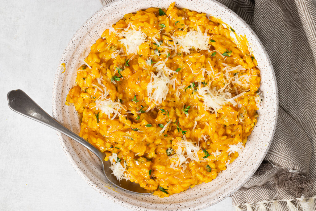 Bowl of Pumpkin Risotto with a spoon in it.