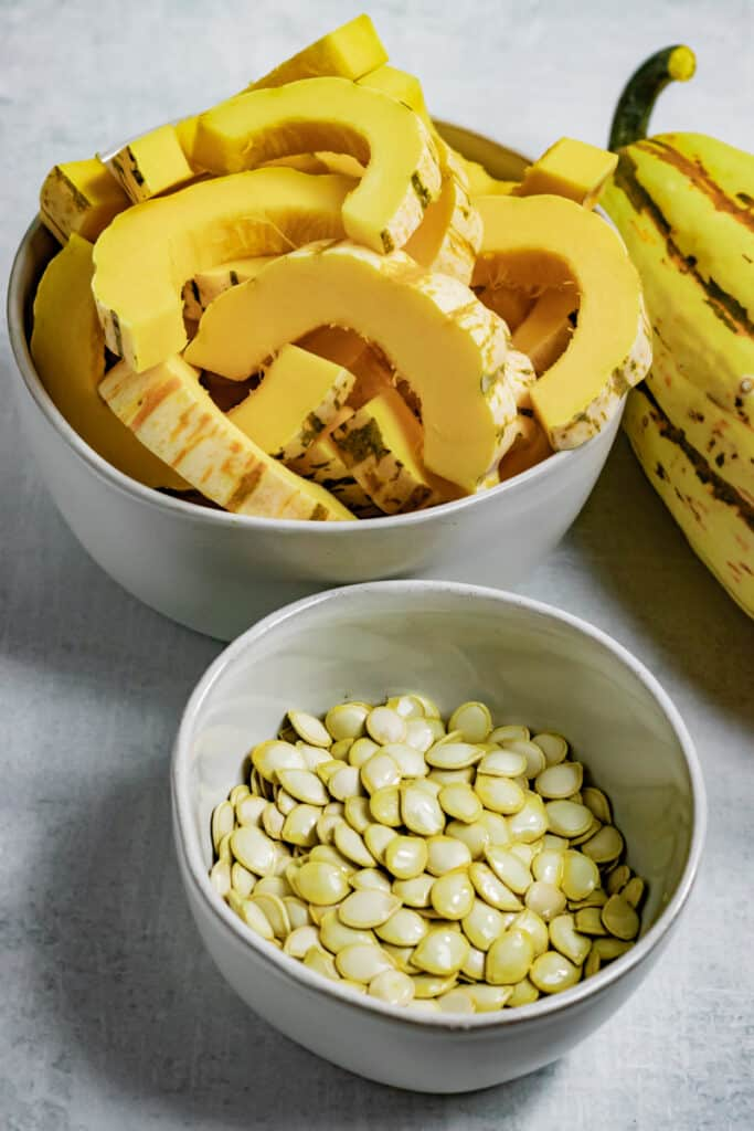 Squash seeds in a bowl next to cut delicata squash