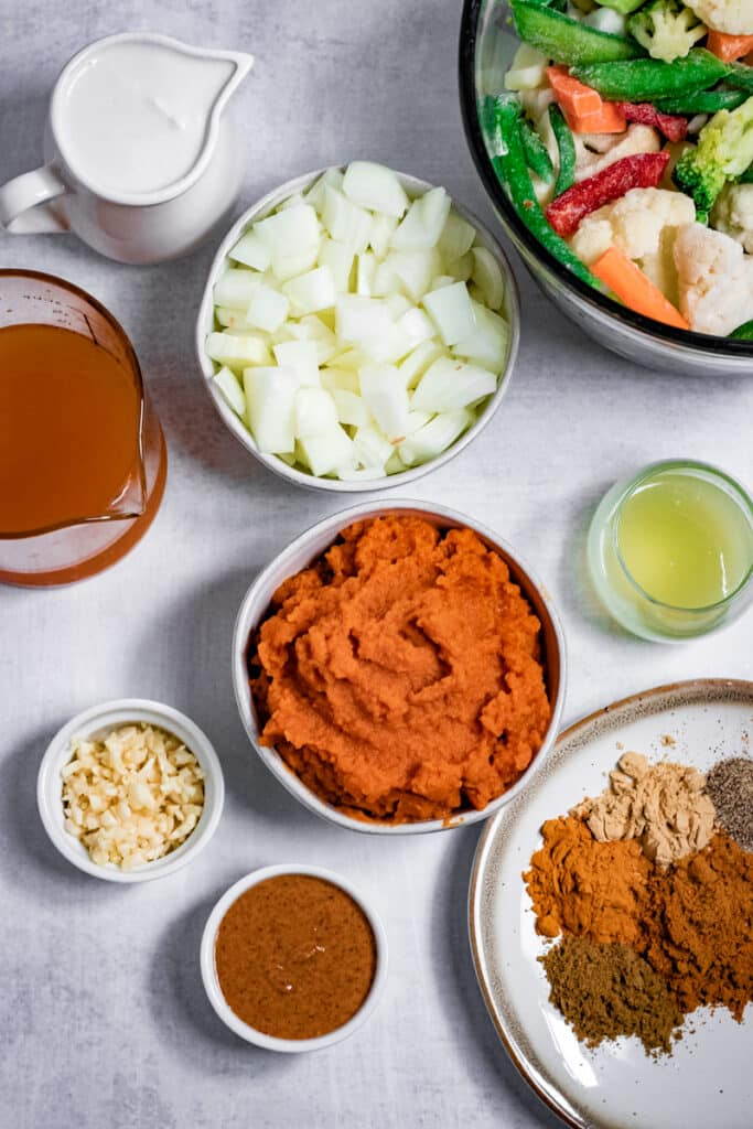 Pumpkin, frozen veggies, diced onions and spices on a table