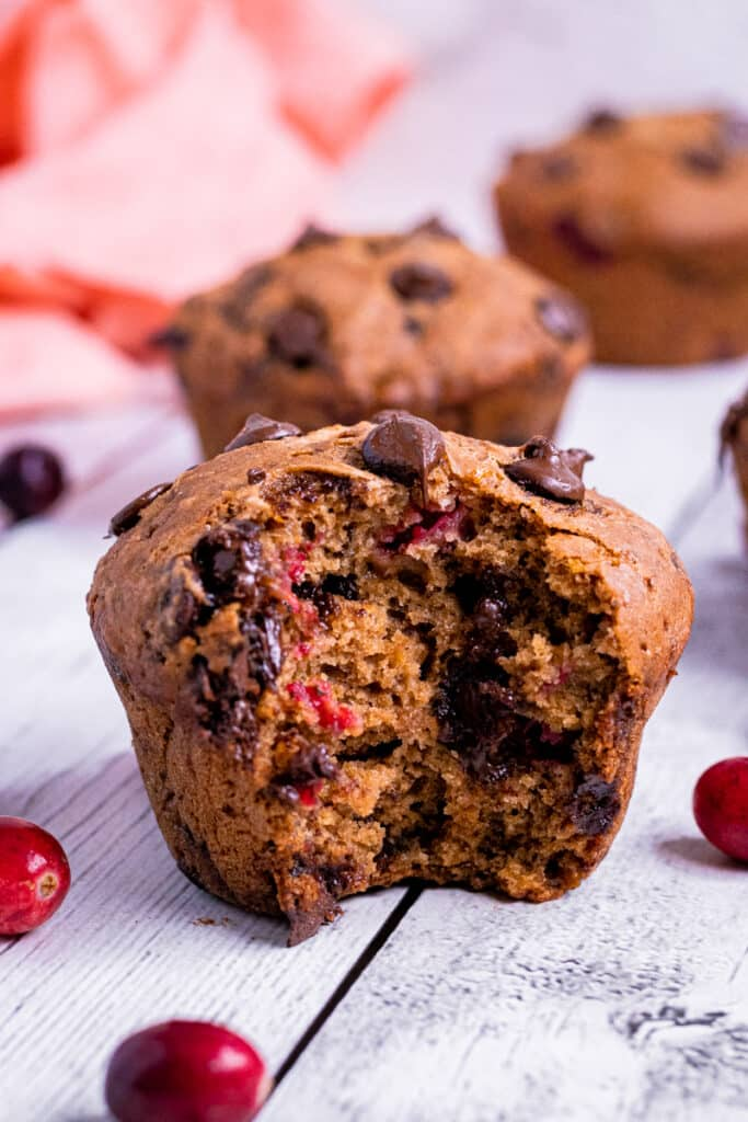 A vegan cranberry muffin with a bite taken out