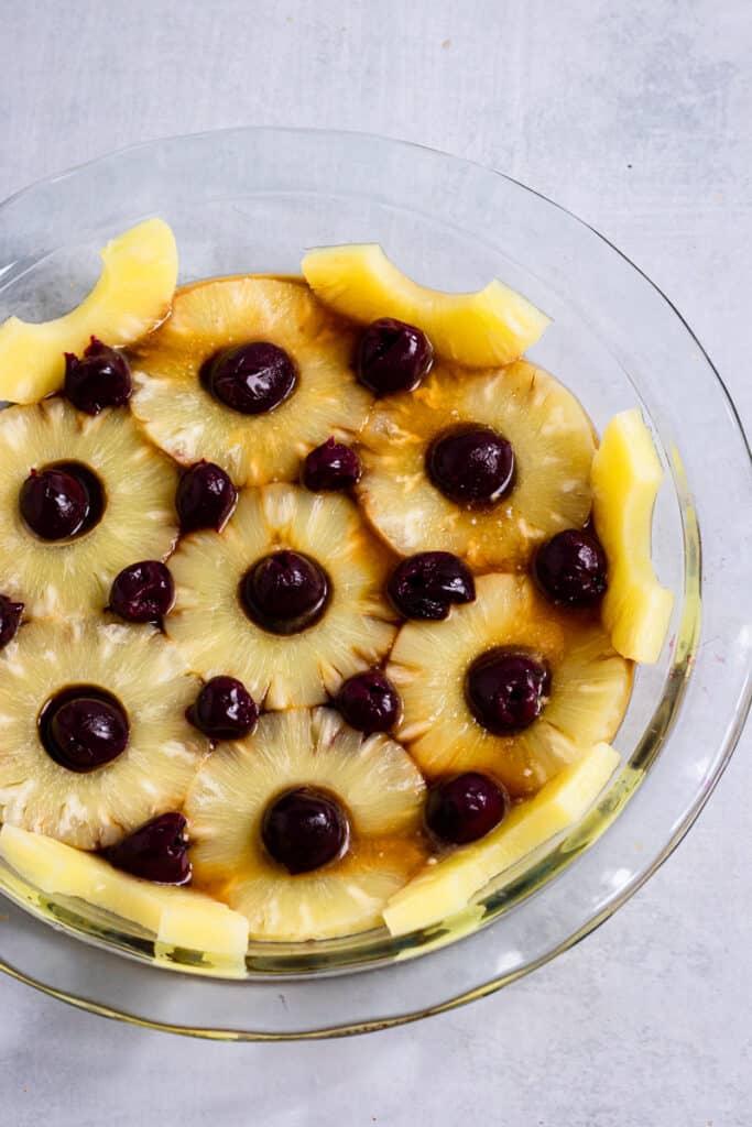 Cherries arranged in between pineapple empty spaces in a pie dish