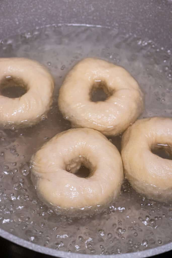 Bagels boiling in a pot of water