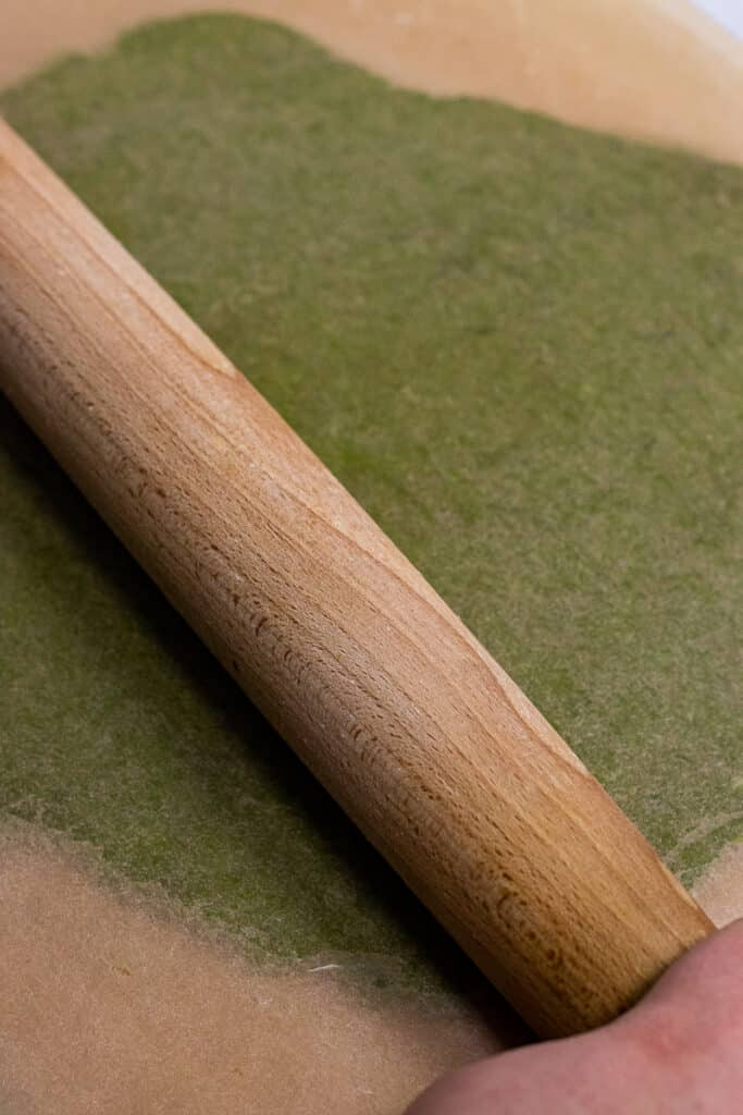 Cookie dough being rolled out between two sheets of parchment paper