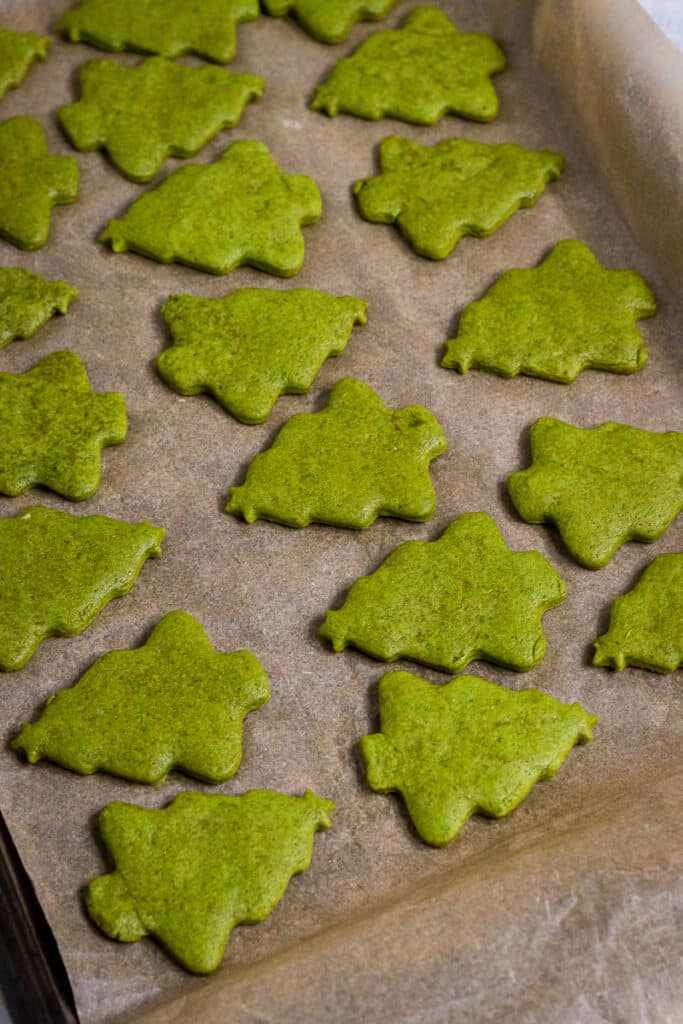 Unfrosted matcha cookies on a baking tray