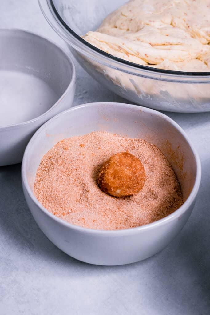 A dough ball covered in a cinnamon sugar mix