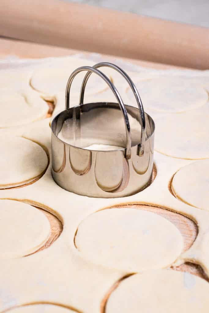 Using a biscuit cutter to cut holes in dough