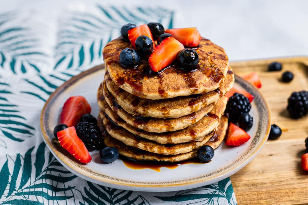 Plant-based pancakes covered in fruit and date syrup