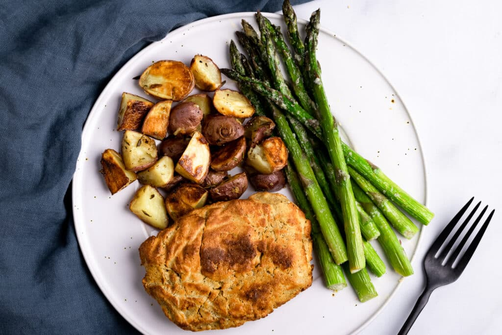 Seitan Chicken on a plate with roasted potatoes and asparagus