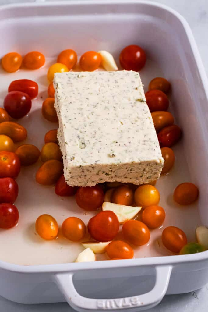 Uncooked vegan feta in a tomato filled baking tray