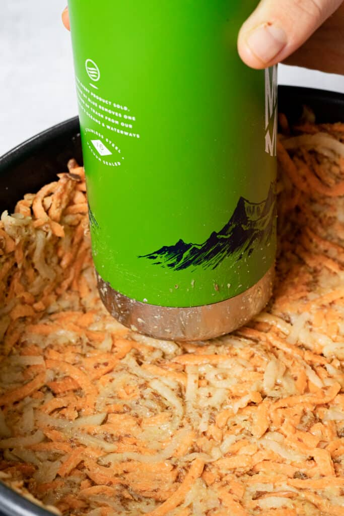 Using a metal water bottle to press crust into shape