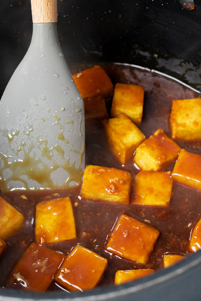 Mixing the baked tofu with the sauce