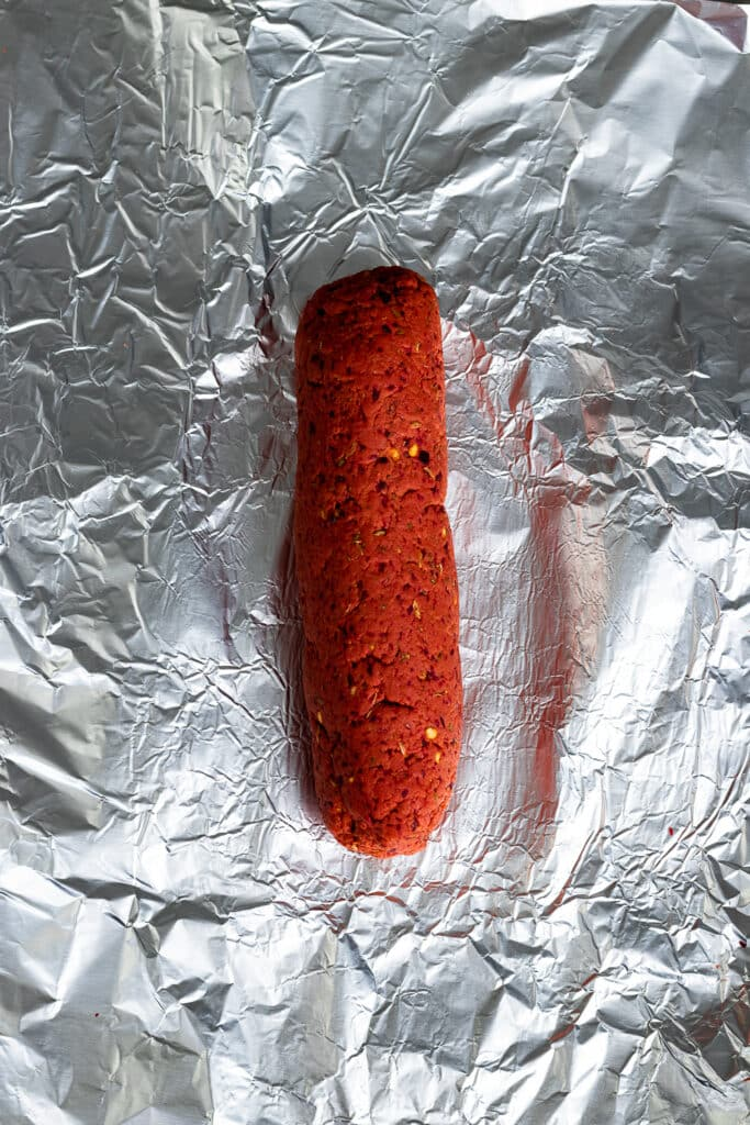 Meat mixture formed into a stick and placed on aluminum foil