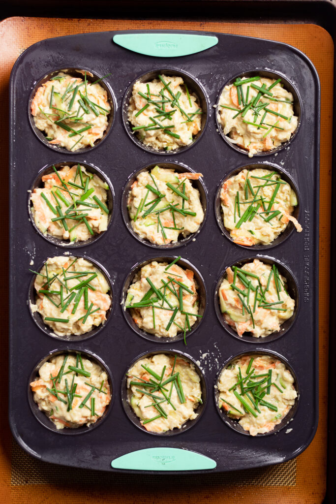 Unbaked muffins in a silicon tray topped with chives